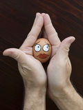 Lady egg face in man hand Stock Photo
