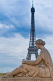 The Lady and the Eiffel Tower. A statue of a woman resting with a view of the Eiffel Tower in Paris on a stormy spring day Royalty Free Stock Image