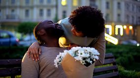 Lady embracing boyfriend, looking with love, holding flowers, romantic date royalty free stock image