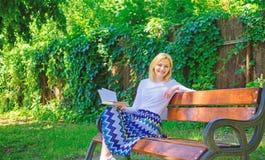 Lady enjoy poetry in garden. Enjoy rhyme. Woman happy smiling blonde take break relaxing in garden reading poetry. Girl royalty free stock photo