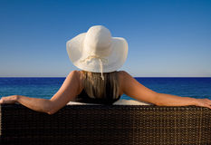 Lady enjoying a perfect view to the ocean. Lady with hat sitting on a bench and enjoying a perfect view to the ocean Stock Images