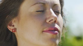 Lady enjoying wind with closed eyes, serenity, calm woman senses oneness nature