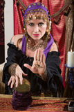 Lady with Evil Eye Curse. Mysterious female fortune teller showing an evil eye in palm Royalty Free Stock Photos
