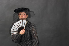 Lady with a fan. The lady in a veil, in a black dress, with a white fan Stock Photography