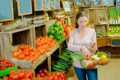 Lady in farm shop holding basket produce. Lady in farm shop holding basket of produce Stock Image