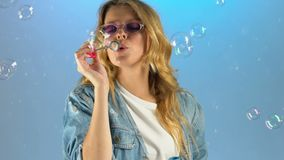 Lady in fashion glasses making soap bubbles, having fun, glasses for every taste. Stock footage stock video