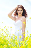 Lady in field. Young lady wearing white dress standing in field royalty free stock photos