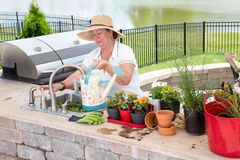 Lady filling a watering can on an outdoor patio Stock Photos