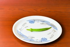 Lady finger okra in white plate closeup on isolated background. Lady finger okra vegetables in plate white food green fresh organic closeup on isolated stock images