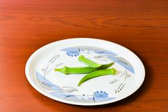 Lady finger okra in white plate closeup on isolated background. Lady finger okra vegetables in plate white food green fresh organic closeup on isolated royalty free stock photo