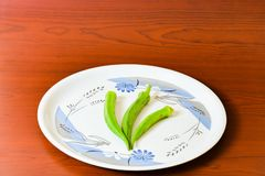 Lady finger okra in white plate closeup on isolated background. Lady finger okra vegetables in plate white food green fresh organic closeup on isolated royalty free stock image