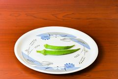 Lady finger okra in white plate closeup on isolated background. Lady finger okra vegetables in plate white food green fresh organic closeup on isolated stock image
