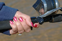 Lady Fisherman's Hands. A lady holds a fishing rod and reel at the lake Stock Photography
