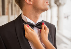Lady fixing man's bow tie Royalty Free Stock Images