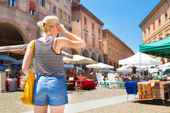 Lady on flea market in Bologna, Italy. Lady walking the flea market on old traditional Piazza of Santo Stefano square of Bologna, Italy Stock Photos