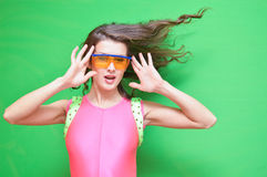 Lady with flipping hair wearing safety glasses and. Closeup portrait of amazing brunette female with flipping curly hair in tight pink jumpsuit touching her Royalty Free Stock Photo