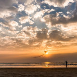 Lady flying a kite on the sunset on Goa beach Royalty Free Stock Images