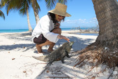 Lady fondle Cuban rock iguana on the beach. Woman cuddle Cuban rock iguana on the tropical beach royalty free stock photo