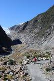 Lady on footpath Franz Josef Glacier New Zealand. Lady with walking pole of footpath by the Waiho river leading up to the Franz Joseph Glacier Kā Roimata o Hine Stock Photos