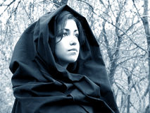 Lady of the forest. Beautiful woman with black cap and hood in the woods Royalty Free Stock Photo