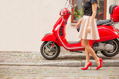 Lady in front of red moto scooter Royalty Free Stock Photography