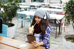 Lady in funny volume hat sitting on cafe and drinking banana cocktail royalty free stock photography