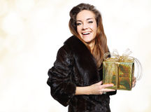 Lady in a fur coat with a gold gift Stock Image