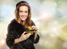 Lady in a fur coat with a gold gift Stock Photos