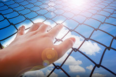 Lady or girl hand catching iron bar with sky and clouds background, imprison feeling. Lady or girl hand catching iron bar with sky and clouds background, freedom royalty free stock image