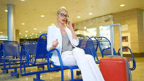 Lady in glasses and with luggage speaks by phone the waiting room. stock footage