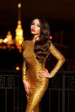 Lady in golden shining dress Stock Images
