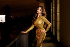 Lady in golden shining dress Stock Photos
