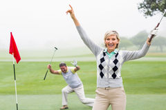 Lady golfer cheering at camera with partner behind Stock Photos