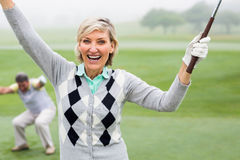 Lady golfer cheering at camera with partner behind. On a foggy day at the golf course Stock Photo