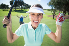Lady golfer cheering at camera with partner behind Stock Image