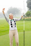 Lady golfer cheering. On a foggy day at the golf course Stock Photos