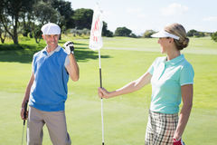 Lady golfer holding eighteenth hole flag for cheering partner. On a sunny day at the golf course Royalty Free Stock Photography