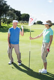 Lady golfer holding eighteenth hole flag for cheering partner Stock Photos