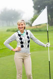 Lady golfer holding flag. On a foggy day at the golf course Royalty Free Stock Photography