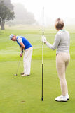 Lady golfer holding flag for partner putting ball Royalty Free Stock Images