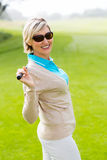 Lady golfer holding her club behind her head Stock Image