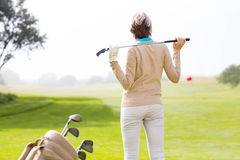 Lady golfer holding her club behind her head Royalty Free Stock Images
