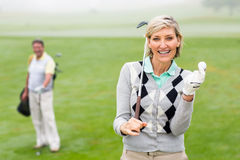 Lady golfer smiling at camera with partner behind. On a foggy day at the golf course Royalty Free Stock Photos