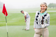 Lady golfer smiling at camera with partner behind. On a foggy day at the golf course Royalty Free Stock Photo