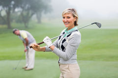 Lady golfer smiling at camera with partner behind. On a foggy day at the golf course Stock Photography