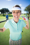 Lady golfer smiling at camera with partner cheering behind Stock Images