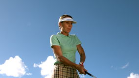 Lady golfer swinging her club stock video
