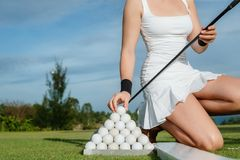 Golfer player. Lady golfer taking her white ball from ball set Stock Image