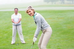 Lady golfer teeing off for the day watched by partner Royalty Free Stock Images