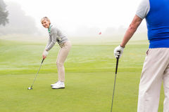 Lady golfer teeing off for the day watched by partner Stock Photo